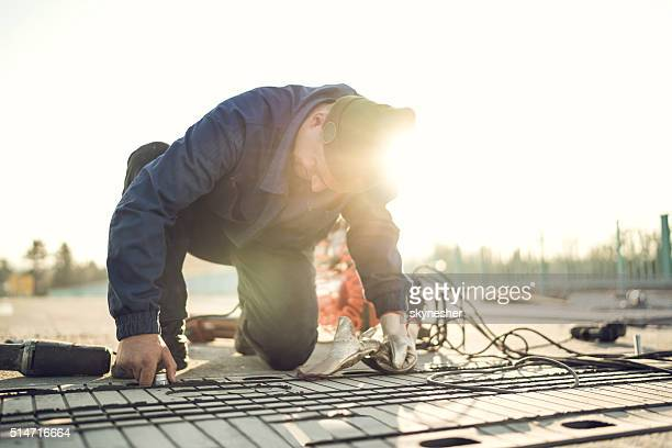 Manual worker installing metal part on road construction at sunset.