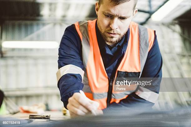 Manual worker marking on sheet metal in industry