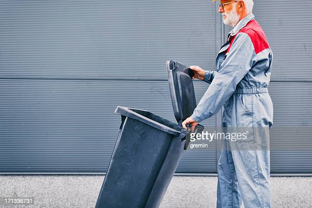 manual worker moving dustbin - industrial storage bins stock pictures, royalty-free photos & images