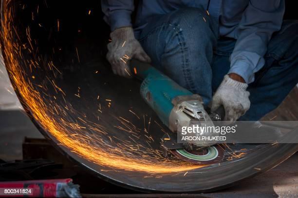 Manual worker on a workshop grinding big steel pipe