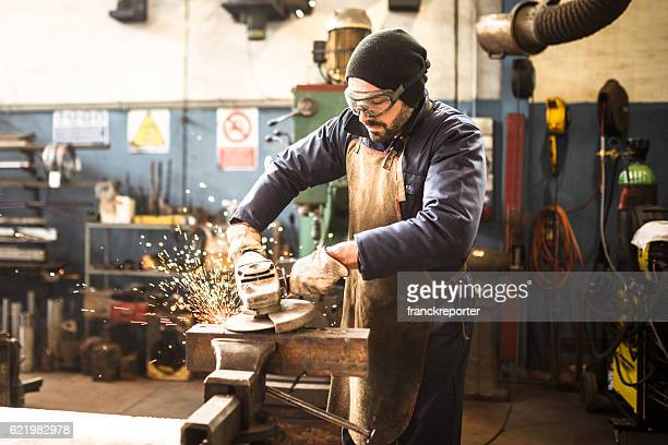 manual worker on a workshop with the grinder