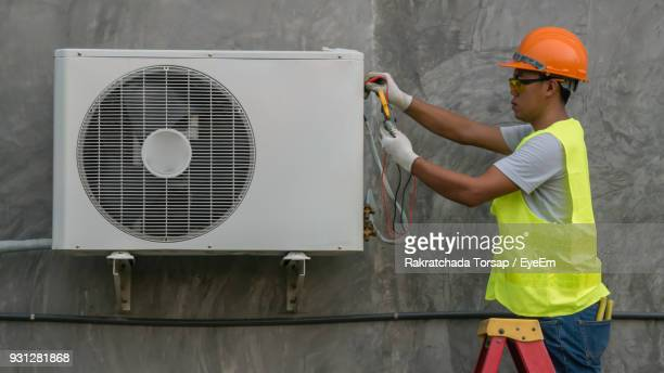 manual worker repairing air conditioner against wall - hvac stock photos and pictures