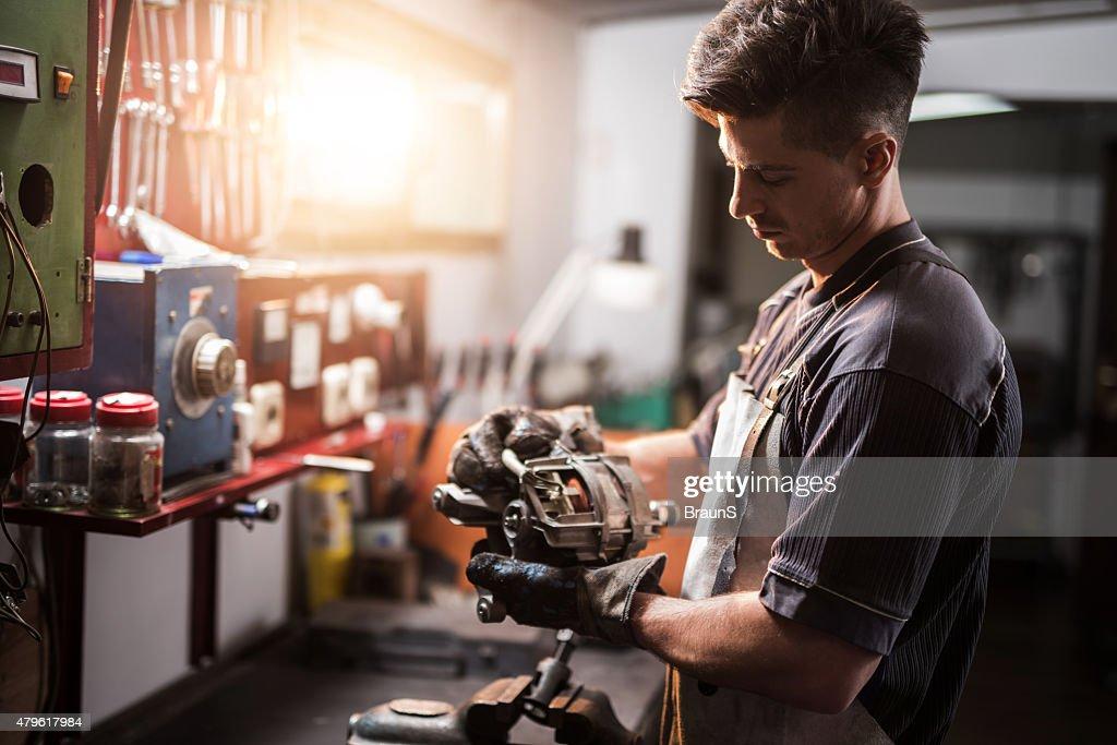 Manual worker repairing electric motor in a workshop. : Stock Photo