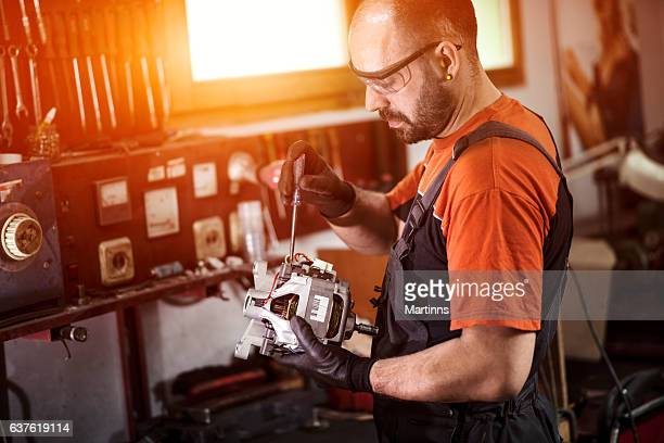manual worker repairing electric motor in a workshop. - electric motor stock photos and pictures