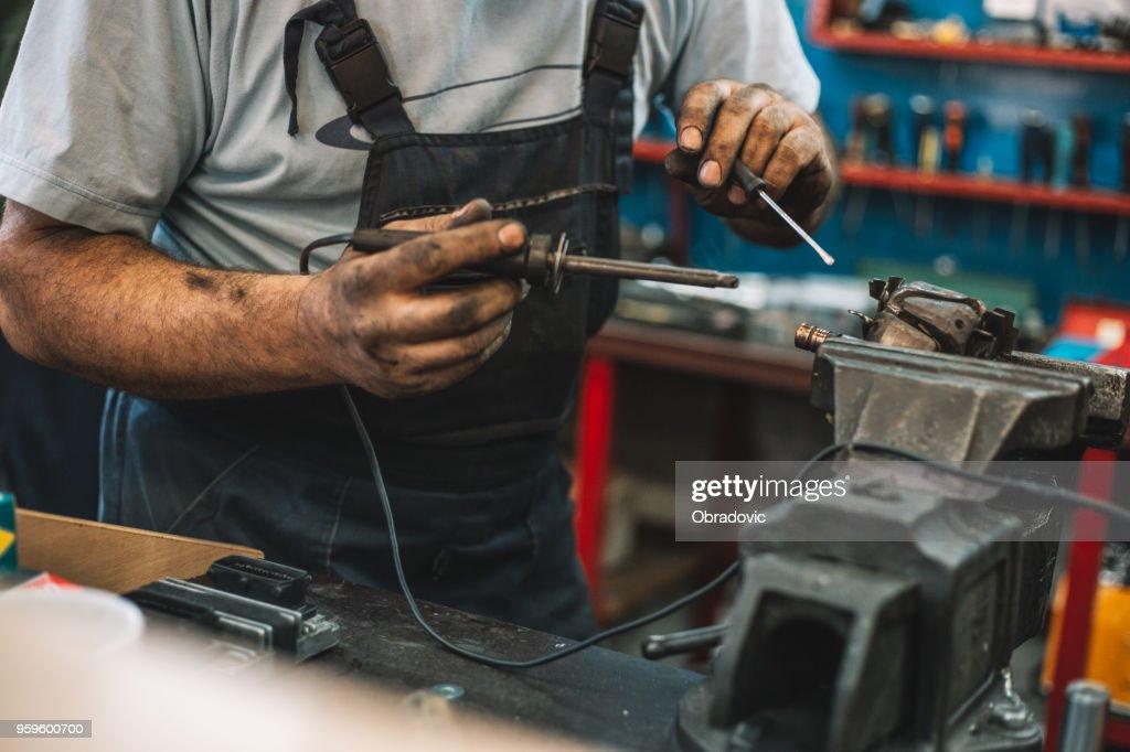 Manual worker repairing electric motor in a workshop : Stock Photo