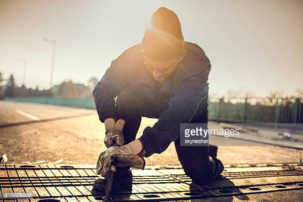 Manual worker repairing road on a bridge at sunset.