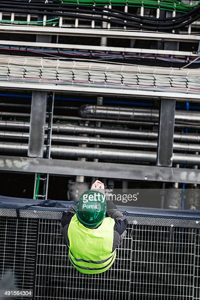 Manual worker standing on metal grate in factory