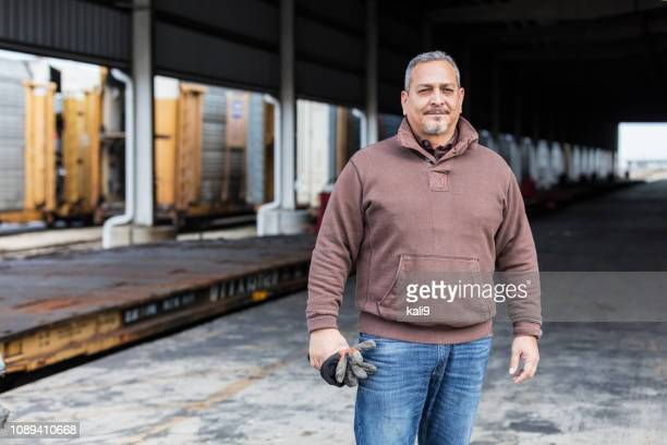 manual worker standing outdoors at shipping port - serious stock pictures, royalty-free photos & images