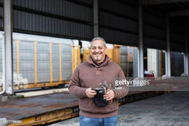 manual worker standing outdoors at shipping port - working class stock pictures, royalty-free photos & images
