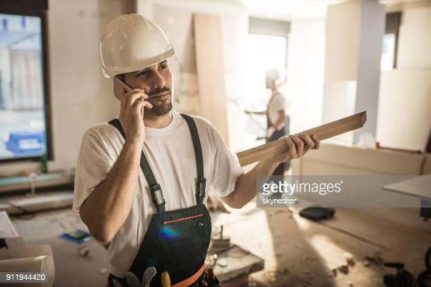Telefonieren mit Handy auf Baustelle Arbeiter.