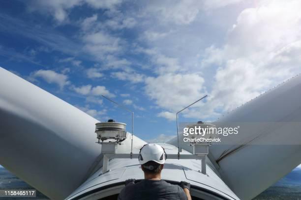 manuell arbetare tekniker på vindkraftverk högt upp mellan bladen - vindkraftverk bildbanksfoton och bilder