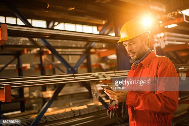 Manual worker text messaging on cell phone in aluminum mill.