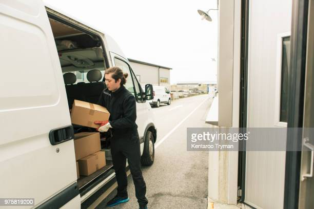 Manual worker unloading boxes from delivery van
