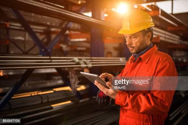 肉体労働者産業建物内デジタル タブレットを使用しています。