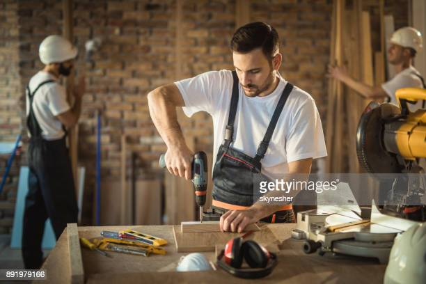 manual worker using drill while making home improvements on construction site. - drill stock pictures, royalty-free photos & images