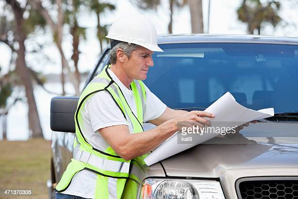 manual worker wearing hardhat and safety vest - real estate developer stock pictures, royalty-free photos & images