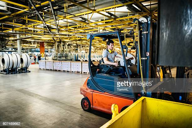 Manual Worker with forklift in a factory