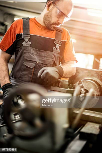 Manual worker working on a machine in a workshop