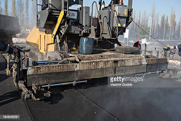 Manual workers controlling large road surfacing machine being trailed by articulated lorry