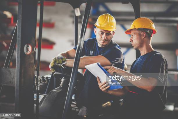 manual workers cooperating while reading reports in a warehouse. - land vehicle stock photos and pictures