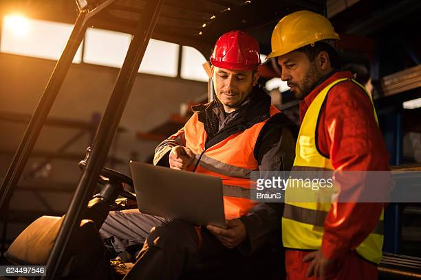 Manual workers cooperating while working on a laptop.
