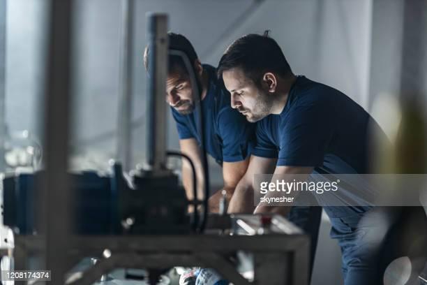 arbeiter, die während der arbeit an einer maschine in einer fabrik zusammenarbeiten. - maschinenbau stock-fotos und bilder