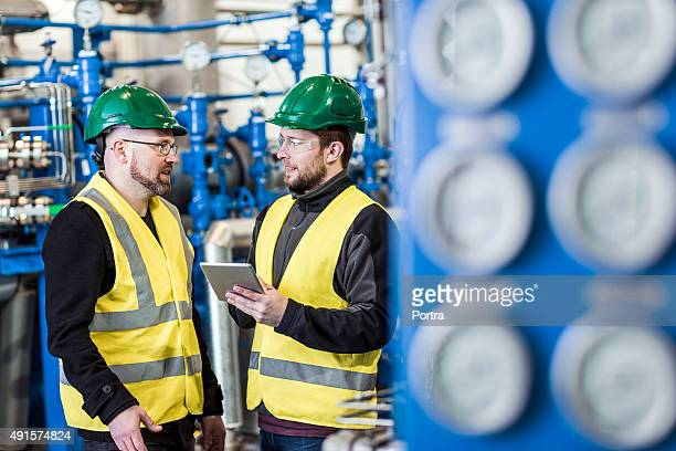 Manual workers discussing in factory