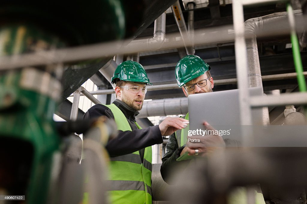 Manual workers discussing while using laptop at factory : Stock Photo