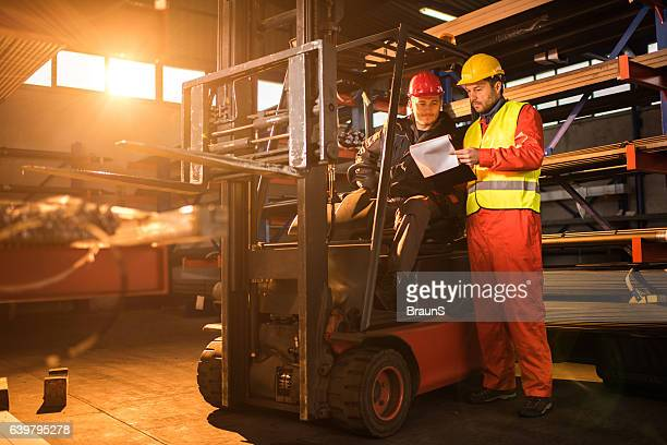 manual workers going through paperwork in aluminum mill. - land vehicle stock photos and pictures