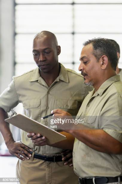 Manual workers looking at clipboard