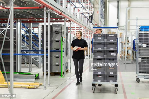 Manual workers moving trolley in a warehouse