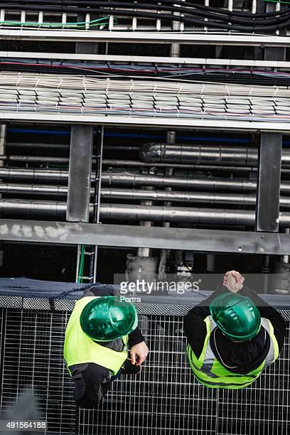 マニュアル員の上に立つメタルグリッドで工場 - metal grate ストックフォトと画像