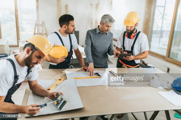 manual workers talking with an architect while going through housing plans on digital tablet. - rebuilding stock pictures, royalty-free photos & images