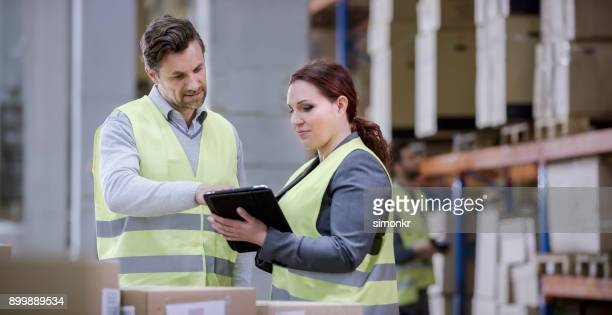 manual workers using digital tablet in warehouse - reflective clothing stock pictures, royalty-free photos & images