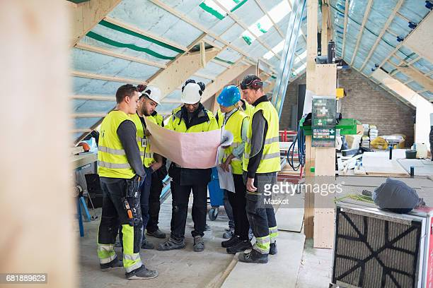 Manual workers with manager reading blue prints at construction site