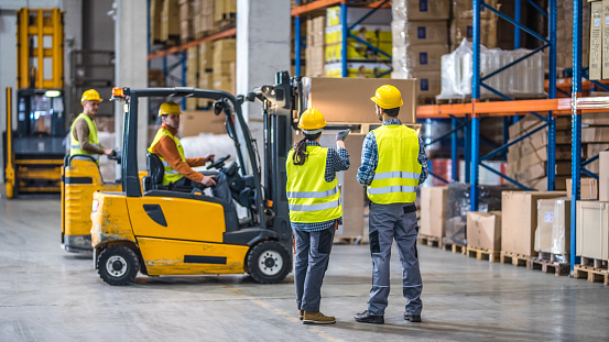 Manual workers working in warehouse 874515358