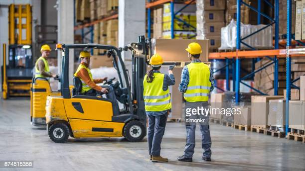 manual workers working in warehouse - safety stock pictures, royalty-free photos & images