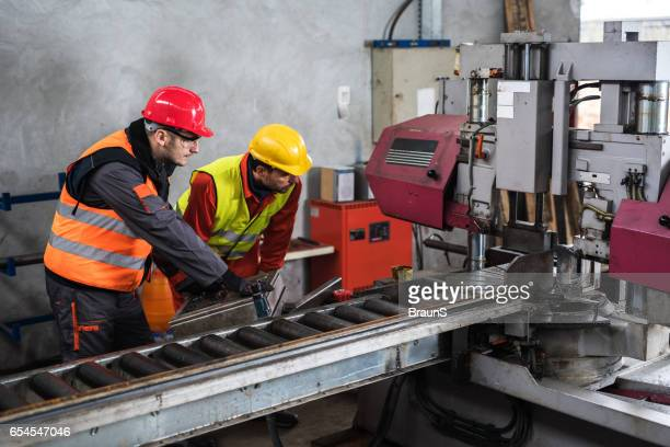 Manual workers working on a machine in factory.