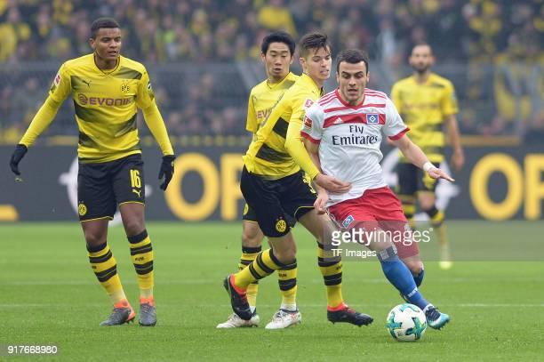 Manuel Akanji of Dortmund and Shinji Kagawa of Dortmund and Julian Weigl of Dortmund and Filip Kostic of Hamburg battle for the ball during the...