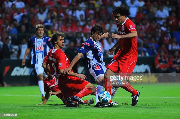 Manuel Alejandro de la Torre Diego Novaretti and Edgar Duenas of Toluca fight for the ball with Dario Cvitanich of Pachuca during a semifinal match...