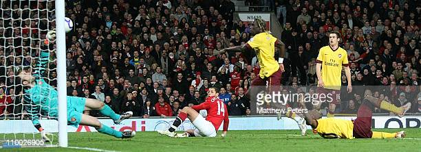 """Manuel Almunia of Arsenal makes a saves from Javier """"Chicharito"""" Hernandez of Manchester United while Johan Djourou of Arsenal lies injured during..."""