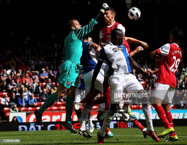Manuel Almunia of Arsenal punches clear under pressure from Chris Samba of Blackburn Rovers during the Barclays Premier League match between...