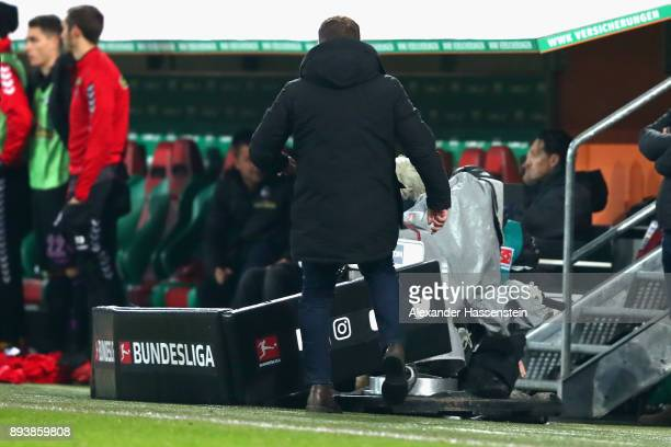 Manuel Baum head coach of Augsburg kicks a TV camera during the Bundesliga match between FC Augsburg and SportClub Freiburg at WWKArena on December...