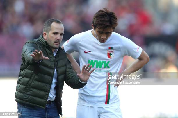 Manuel Baum, head coach of Augsburg talks to his player Ja-Cheol Koo during the Bundesliga match between 1. FC Nuernberg and FC Augsburg at...