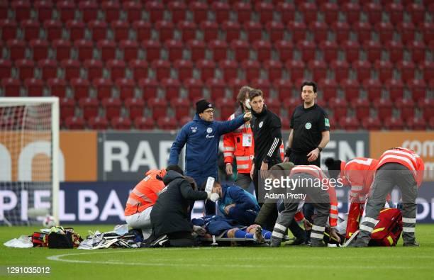 Manuel Baum, Head Coach of FC Schalke 04 checks on Mark Uth of FC Schalke 04 as he receives treatment after a challenge during the Bundesliga match...