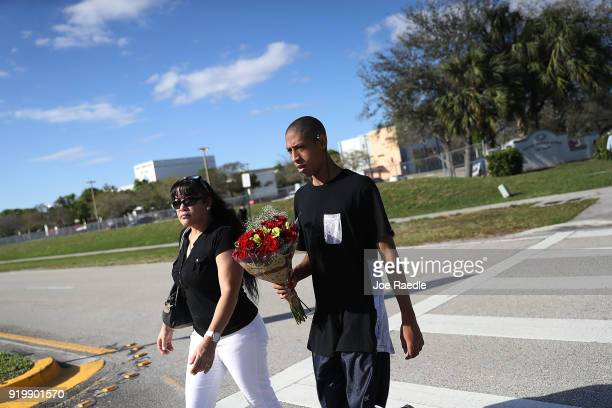 Manuel Cooper a student at the Marjory Stoneman Douglas High School and his mother Serena Fernandez walk near the school on February 18 2018 in...
