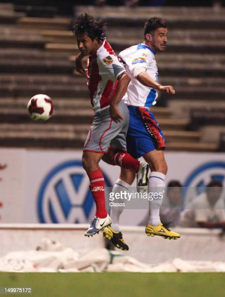 Manuel de la Torre of Lobos struggles for the ball with Matias Abelairas of Puebla during a match between Puebla and Lobos BUAP as part of the Copa...