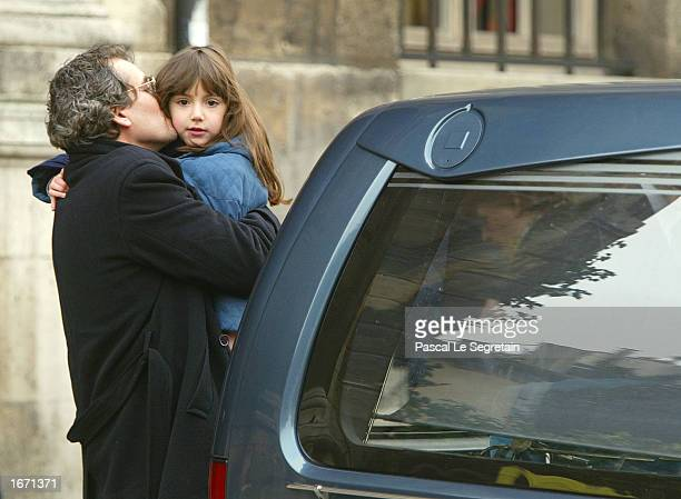 Manuel Gelin kisses his dauther as they attend the funeral service for his father French actor Daniel Gelin December 4 2002 in Paris Gelin known best...