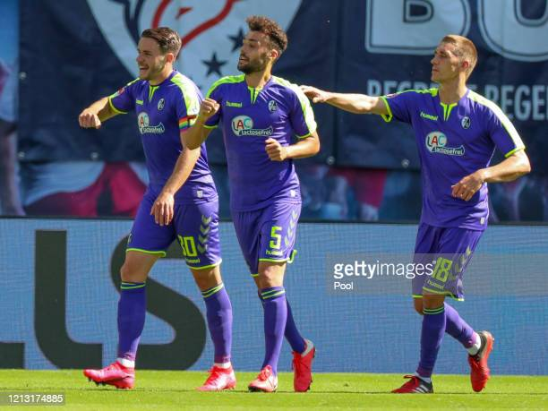 Manuel Gulde of Sport-Club Freiburg celebrates with teammates Nils Petersen and Christian Guenter after scoring their team's first goal during the...