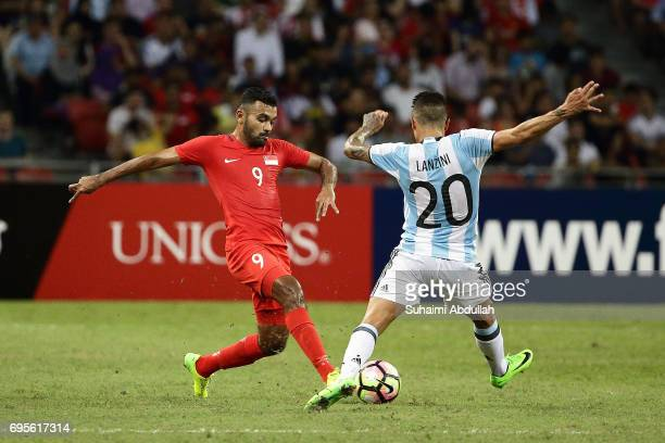 Manuel Lanzini of Argentina and Faritz Hameed of Singapore challenge for the ball during the International Test match between Argentina and Singapore...